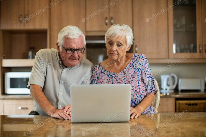 Senior couple using laptop in the kitchen