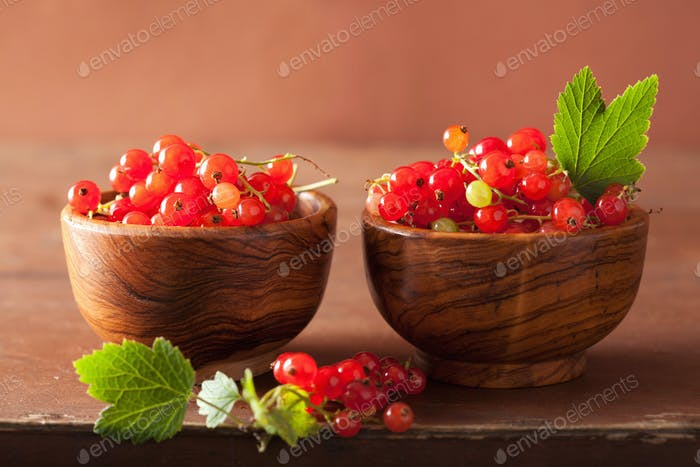 fresh redcurrant in cups over rustic wooden background