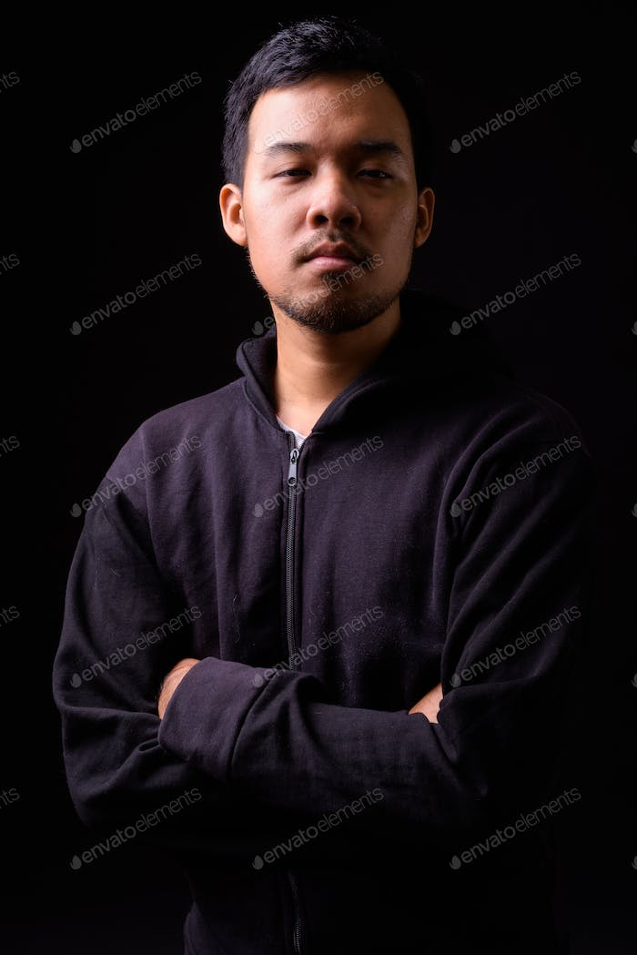 Portrait of young Asian man wearing hoodie with arms crossed