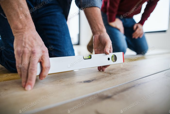 A midsection of man with his father laying vinyl flooring, a new home concept.