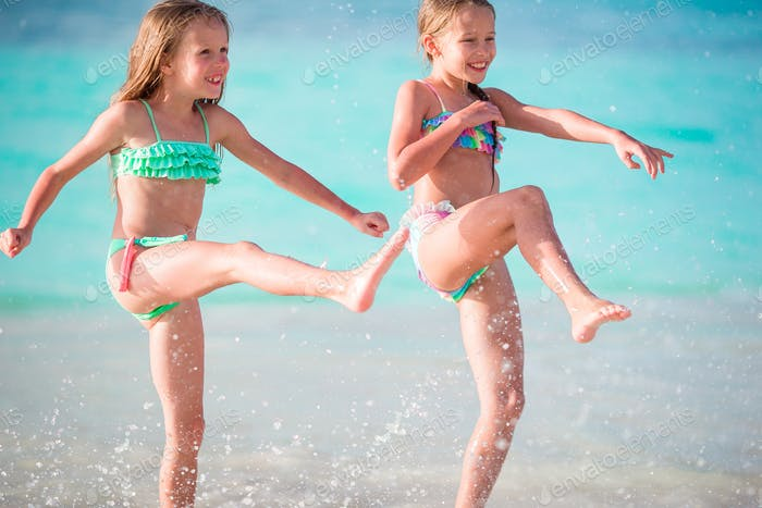 Two little happy girls have a lot of fun at tropical beach playing together at shallow water. Kids