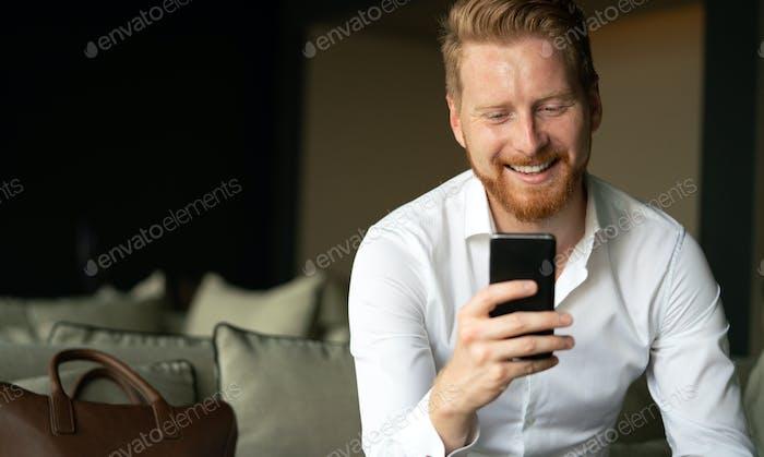 Joven feliz usando su teléfono inteligente en la oficina