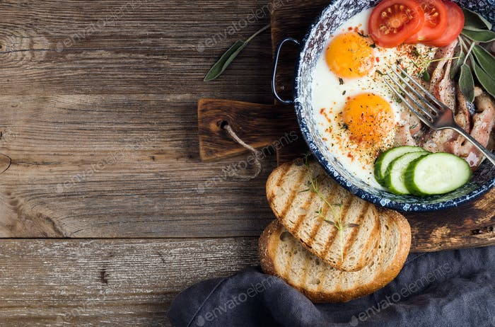 Breakfast set. Pan of fried eggs with bacon, fresh tomato, cucumber, sage and bread