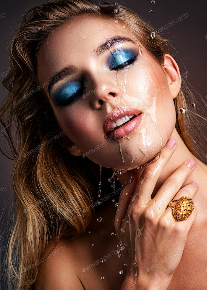 Photo of young woman with style make-up and water splashes