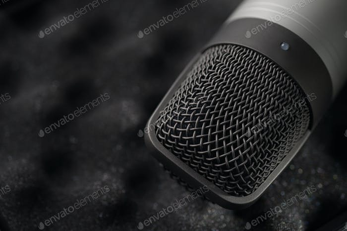 Gray studio condenser microphone on black soft foam