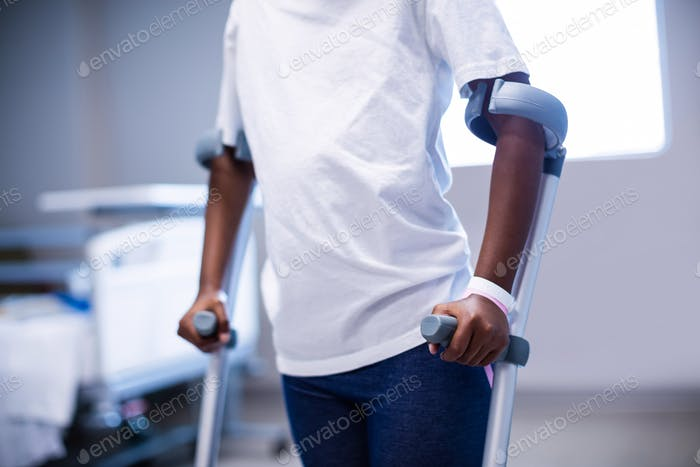 Mid section of girl walking with crutches in ward