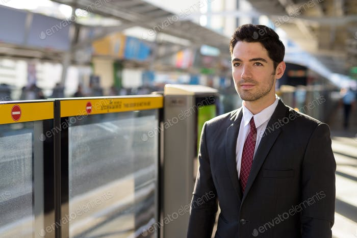 Portrait of businessman standing and waiting at train station platform