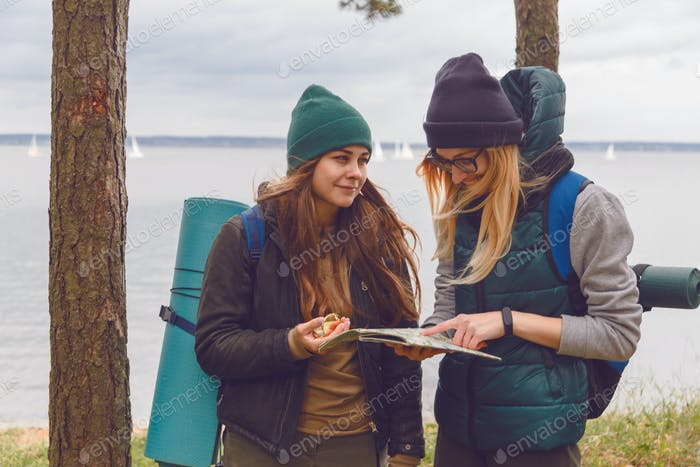 two woman with trendy look searching direction on location map while traveling at wild nature