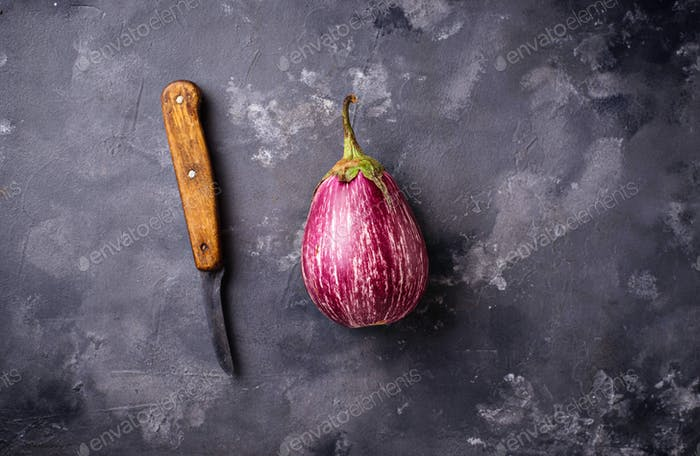 Fresh striped purple aubergines on grey background
