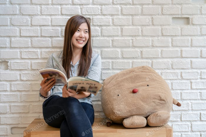 Asian woman in jeans suit sitting and reading the magazine in the living room