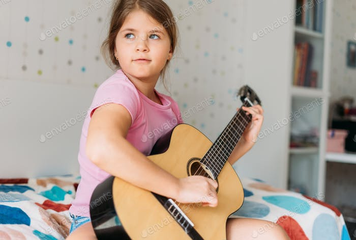 Cute tween girl in pink t-shirt play guitar sit on bed