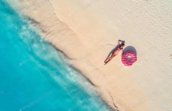 Aerial view of woman with swim ring on the sandy beach