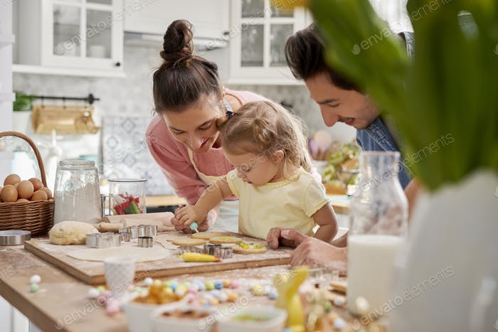 Parents with child decorating cookies for Easter