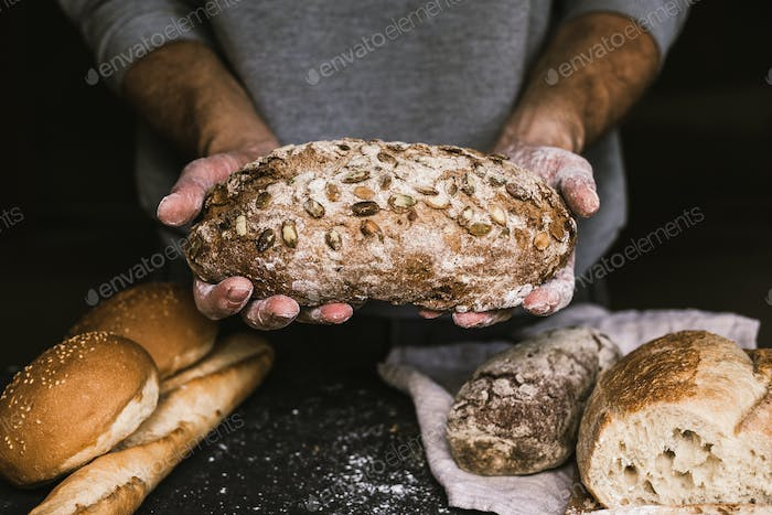 Baker man holding a rustic organic loaf of bread in his hands