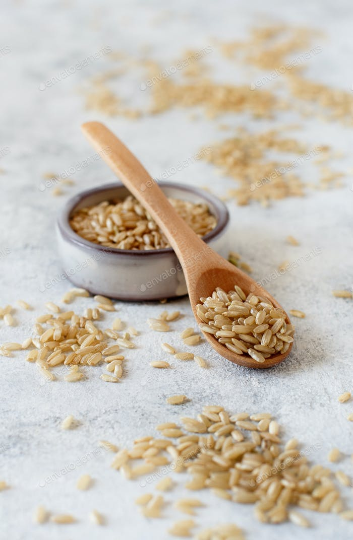 Brown rice in a wooden bowl with a  spoon