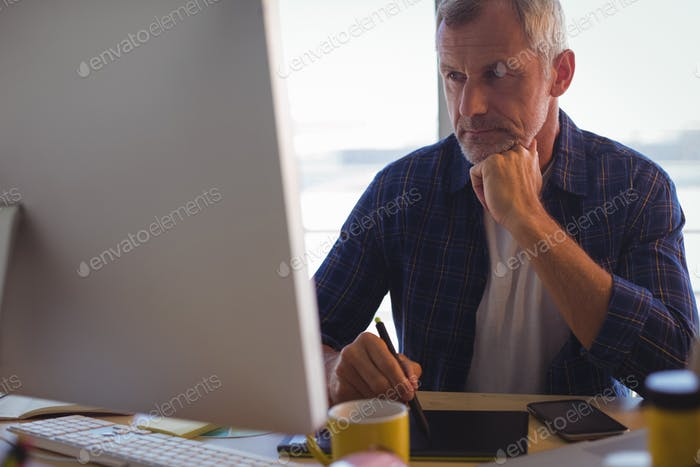 Focused businessman working on digitizer at office desk