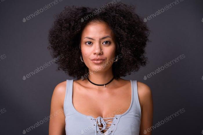 Junge schöne multiethnische Afroamerikanerin vor grauem Hintergrund