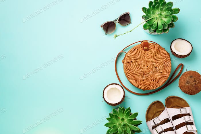Stylish rattan bag, coconut, birkenstocks, succulent, sunglasses on blue background. Banner. Top