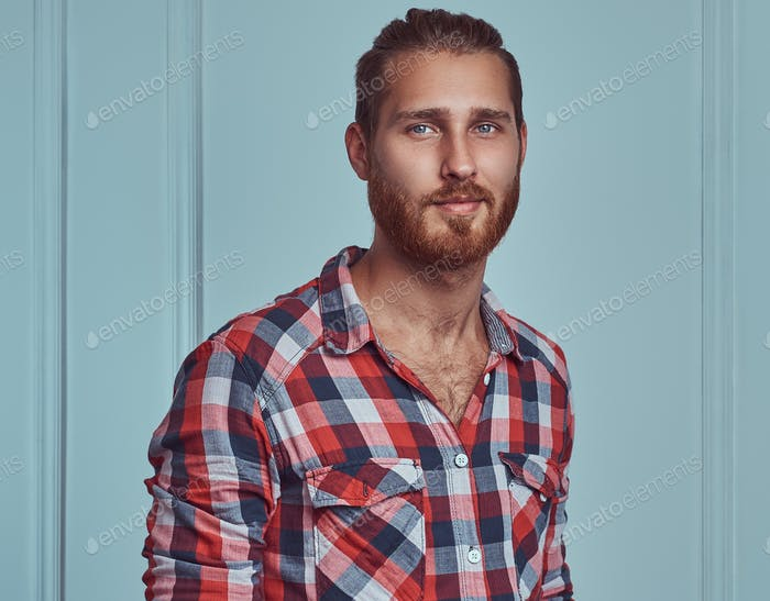 Handsome stylish redhead man in a flannel shirt, posing in a studio against a white wall.