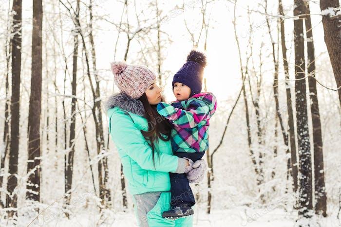 glückliche Familie Mutter und Kind Baby Tochter auf einem Winterspaziergang im Wald