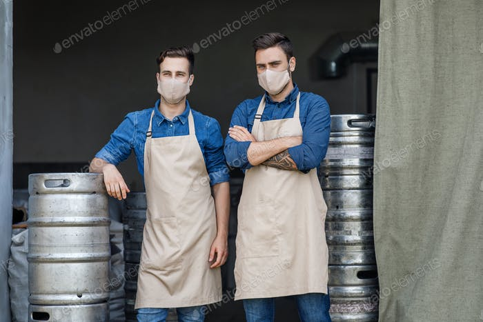 Two handsome men in aprons and protective masks stand in warehouse interior with metal barrels