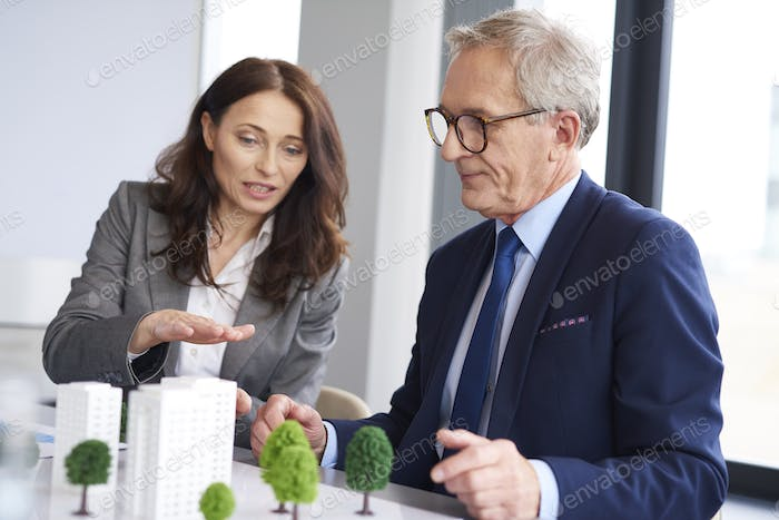 Business couple over architectural model