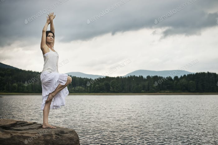 A woman standing on a rock by a lake near Woodstock, New York State, USA