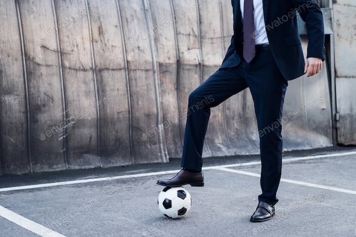 partial view of businessman in suit playing soccer on street