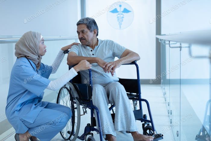 Mixed-race female doctor in hijab interacting with disabled senior