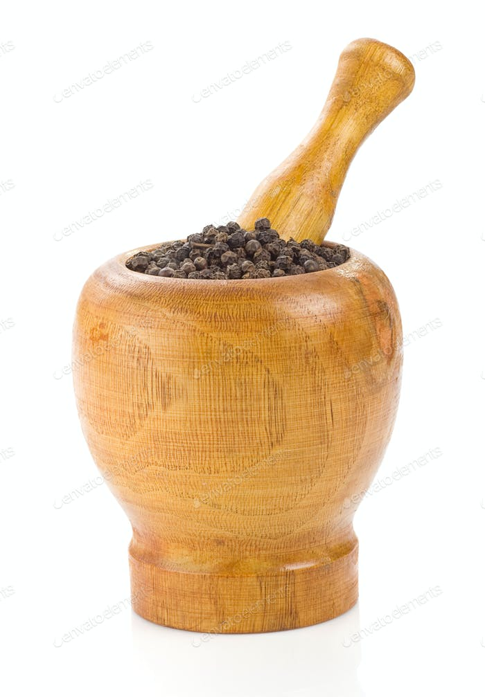 pepper in mortar and pestle on white
