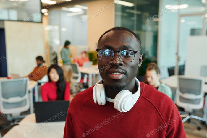 Young serious businessman or designer of African ethnicity talking by smartphone