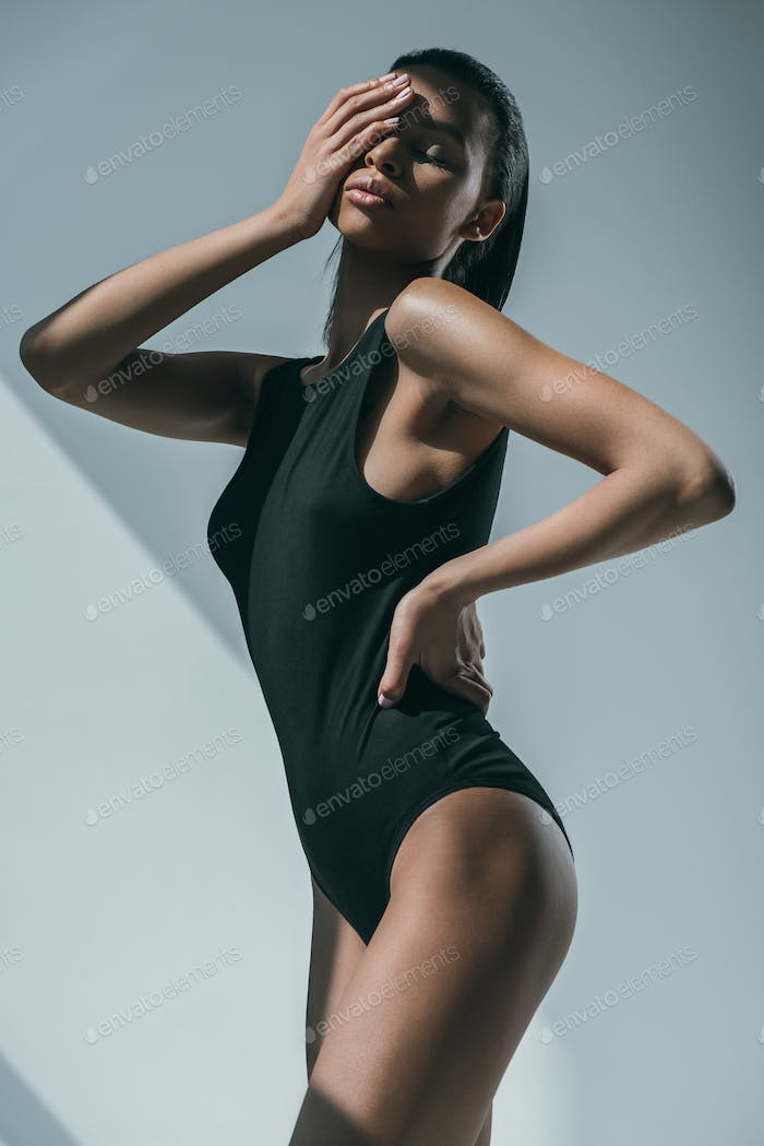 African American Trendy Woman With Slim Body Touching Her Face and Posing in Black Bodysuit