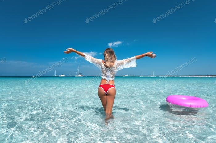 Junge Frau in weißem Spitzenkleid mit rosa Schwimmring im Meer