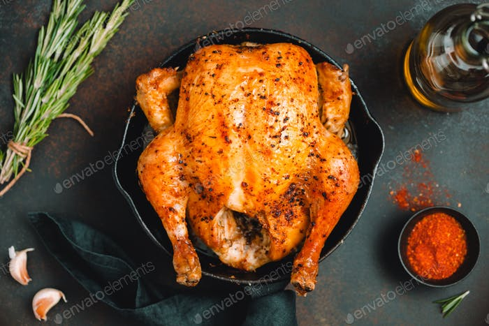 Roasted whole chicken with spices in a black iron skillet on a table.