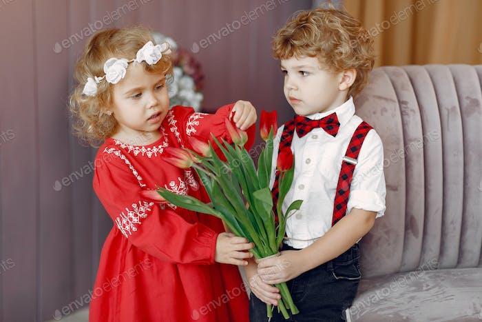 Elegant little kids in a studio with bouquet of tulip