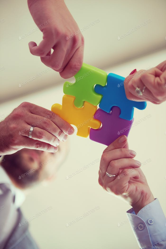 business people group assembling jigsaw puzzle