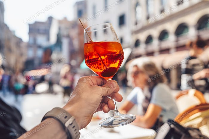 Man's hand with a glass of aperol