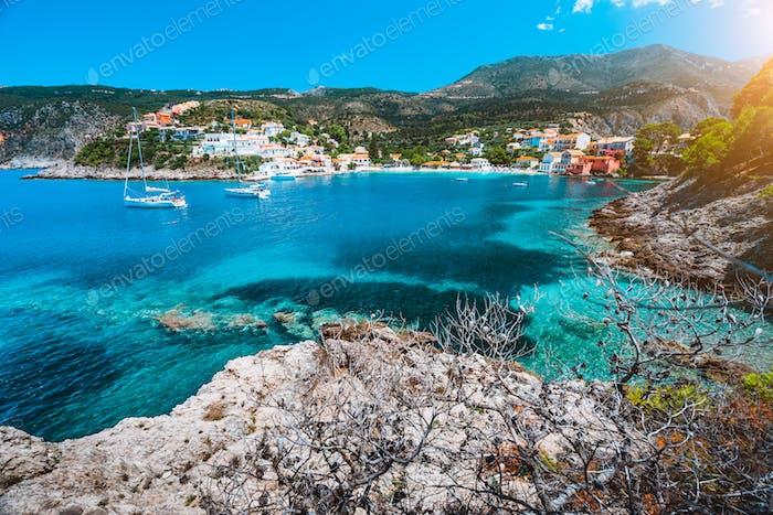 Schönes Dorf Assos, Kefalonia. Griechenland. Weiße Kreuzfahrtschiffe bleiben vor Anker in schönen