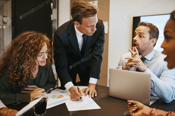 Diverse businesspeople going over paperwork together during an office meeting