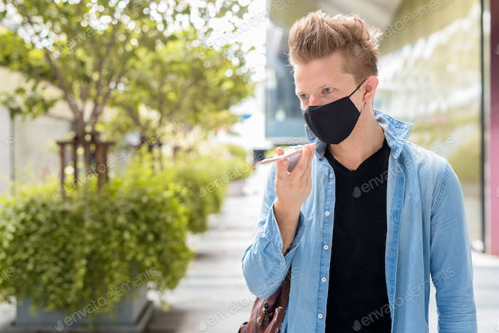 Portrait of man with mask talking on the phone in the city outdoors