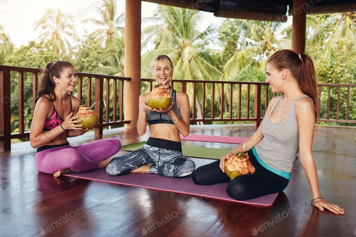 Women relaxing with coconut juice after yoga class