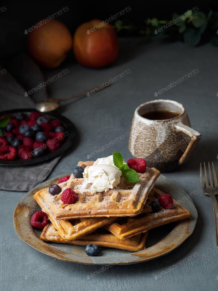 Belgian waffles with raspberries, chocolate syrup. Breakfast with tea on dark background