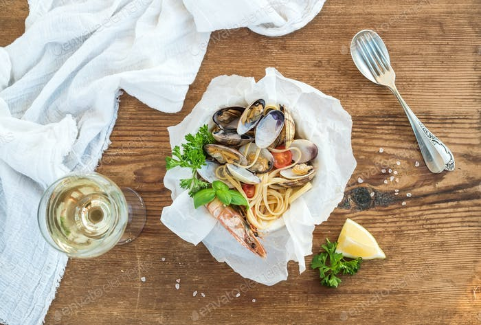 Seafood pasta. Spaghetti with clams and shrimps in bowl, glass of white wine