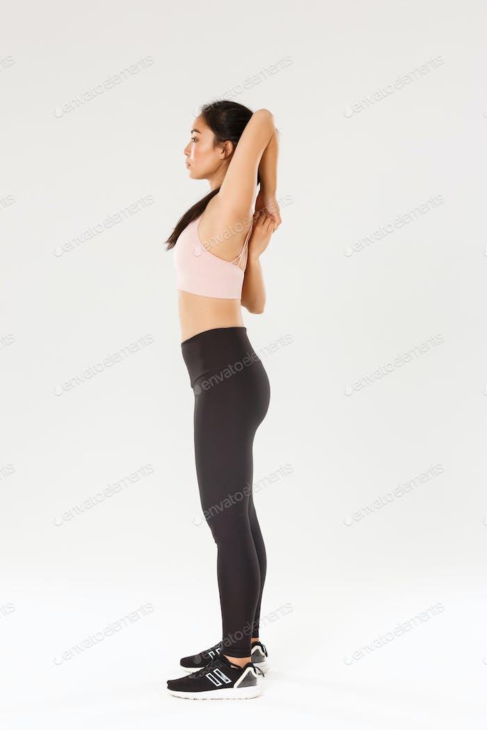 Full length profile of focused strong asian female coach, sportswoman doing fitness exercises