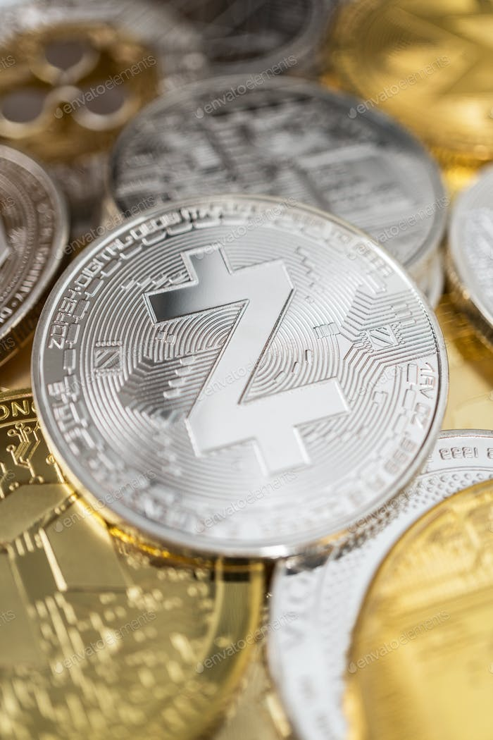 Primer plano de la moneda física de Zcash en la pila de muchas otras criptomonedas