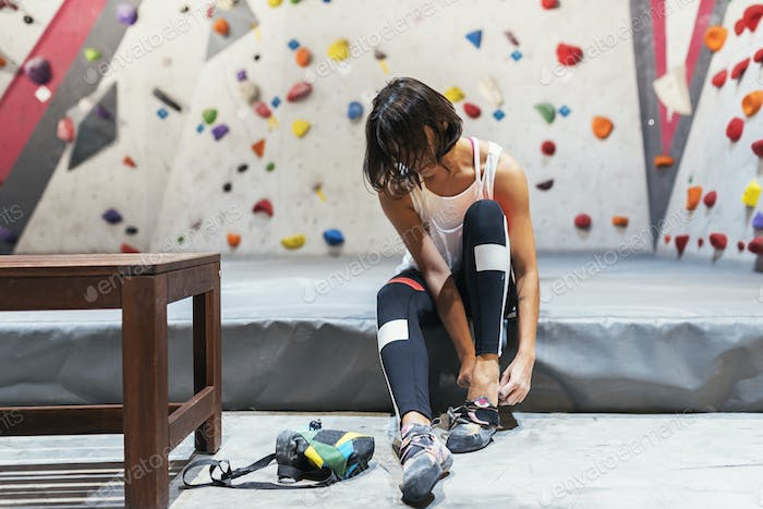 Woman ready for practice rock climbing on artificial wall indoors.