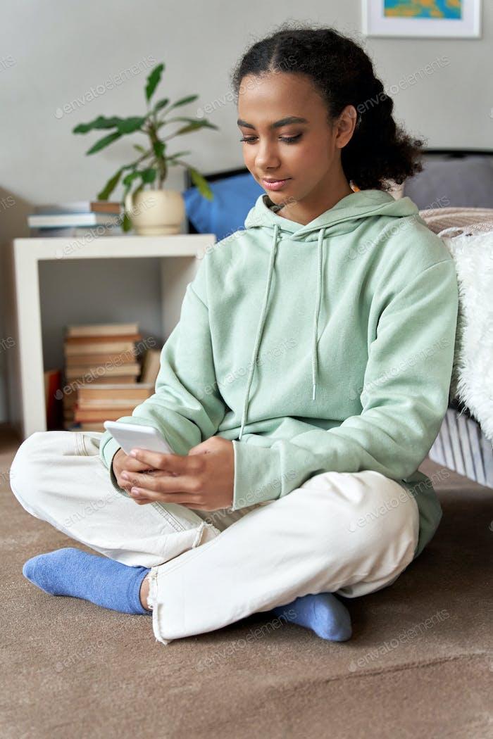 Mixed race teen girl using phone social media apps at home.