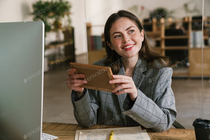 Young smiling woman looking at photo while working in office