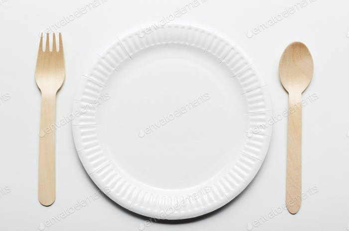 Top view at wooden single use kitchenware and paper plate on whi