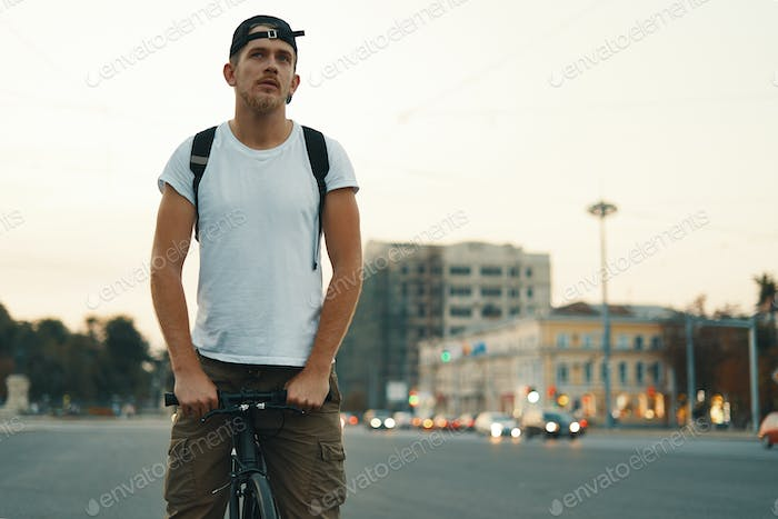 Man riding bicycle in urban city holding hands on handlebar, blurred city in background